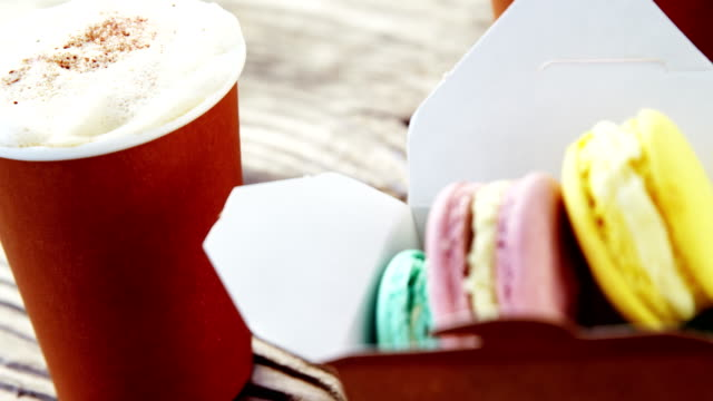 Colorful macaroon cookies in paper bag with coffee video
