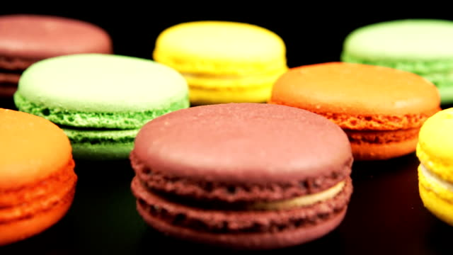 Colorful macaroons is on the black table, tracking video