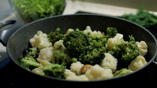 Colorful pea slowly falls to the pan with broccoli and cauliflower. Slow motion. Vegetarian food video