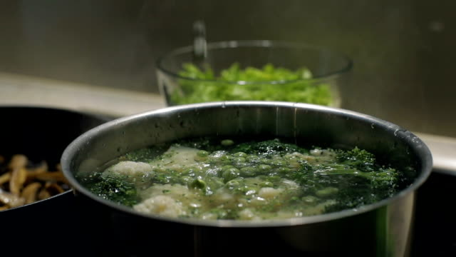 Colorful pea slowly falls to the pot with broccoli and cauliflower in hot water. Slow motion. Vegetarian food video