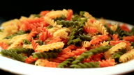 Colorful raw pasta  in a plate video