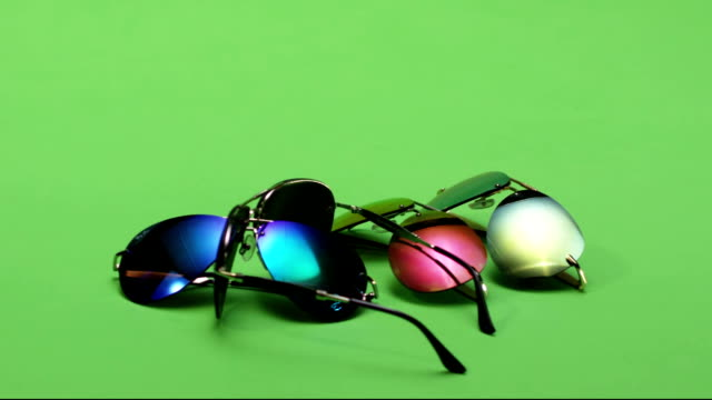 Colorful Sunglasses falling. Falls down. Green screen. Slow Motion. video
