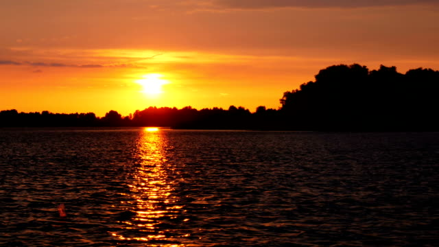 Colour Sunset Over The River With Sun And Orange Clouds video
