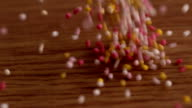 Colourful sprinkles pouring onto surface video