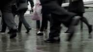 Commuters legs on a rainy street, looped video  COM video