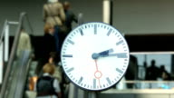 Commuters with clock in the foreground video