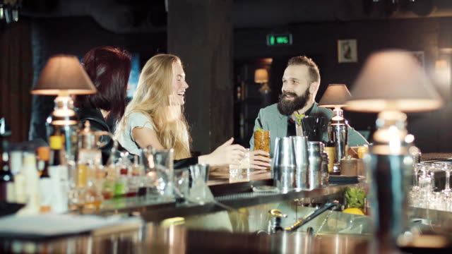 Company of 1 man 2 women are clink glasses in the bar, happy talking and laugh video