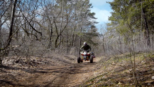 A company of friends is extremely kicking on quad bikes on a country road in the autumn forest, men are leaving the hill performing a trick video