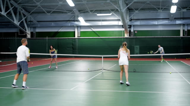A company of friends play tennis on the sports ground, adult men and women throw a tennis ball on different sides of the field video