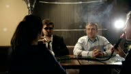 Company people enjoy hookah and communication. HD shot with slider video