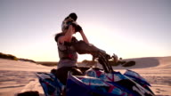 Competitive female quad bike racer looking intent with sun flare video