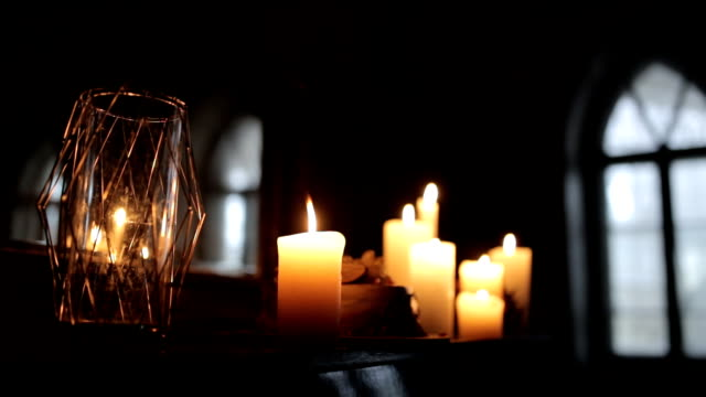 composition of candles on a black piano near a mirror. Candles close-up against the window video