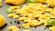 Composition of dry pasta, black pepper, basil and tomatoes video