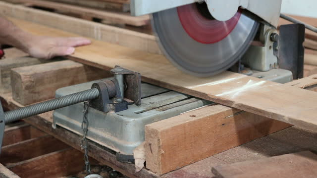 compound miter saw cutting a piece of wood plank in carpentry workshop video