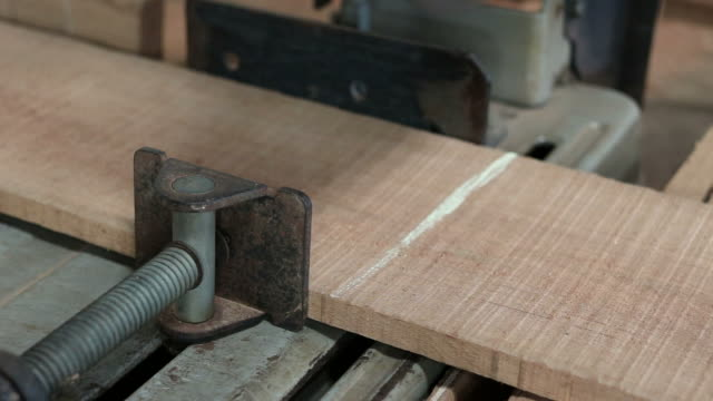 Compound miter saw cutting wood plank in carpentry workshop video