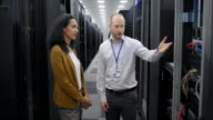 LD Computer engineer showing female visitor the server room video