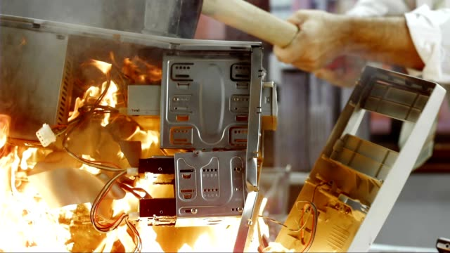 SLO MO LD Computer in flames being hit by hammer video