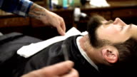 Concentrated Barber shaving beard of client with barber razor video