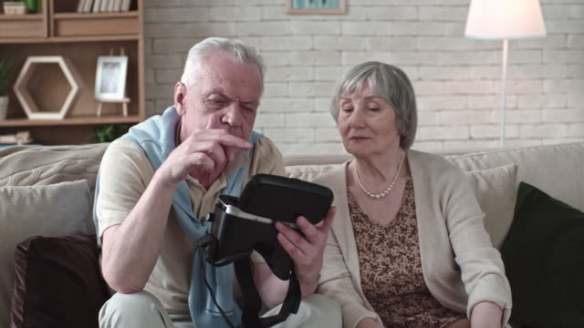 Concentrated Elderly Couple Inspecting VR Goggles video