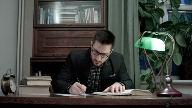 Concentrated male researcher reading book and making notes at the desk video
