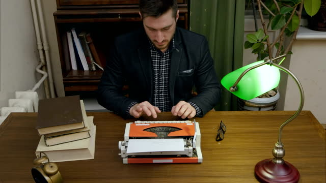 Concentrated writer typing new book on a red vintage typewriter in his cabinet video