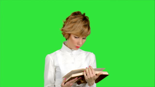 Concentrated young business woman holding and reading book on a Green Screen, Chroma Key video