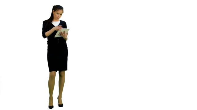 Concentrated young businesswoman using digital tablet on white background video