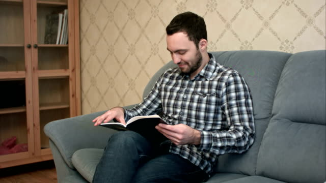 Concentrated young man reading book sitting on the sofa video