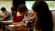 Concentrating students sitting an exam in a classroom video