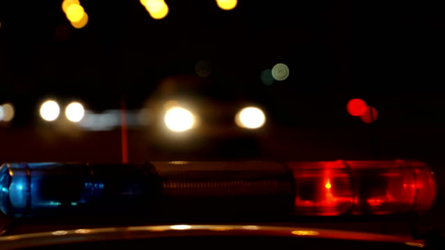 Concept help and rescue. Nihgt city road and flashing lights on top police cruiser close up video