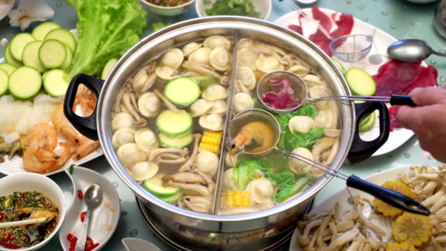 Concept Hotpot Asian cuisine. Cooking shrimp and meat in skimmer spoon. Shrimp in hot soy sauce video