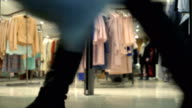Concept mall shopping. Legs silhouette of shoppers on background clothing store. Looped. Bottom view video
