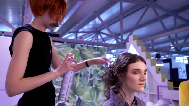 Concept of beauty and fashion. Hairdresser using hairspray for client's hair video