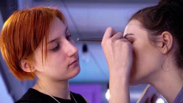Concept of beauty and fashion. Professional makeup artist applying cosmetics on model face. Zoom in video