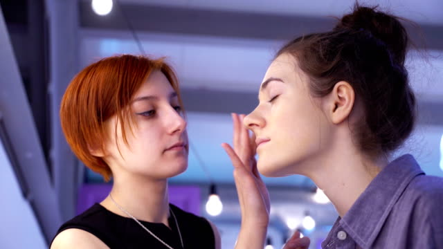 Concept of beauty and fashion. Professional makeup artist applying cosmetics on model face. video