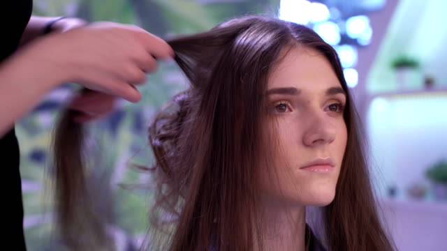 Concept of beauty and fashion. Professional stylist makes curls for young attractive brunette video