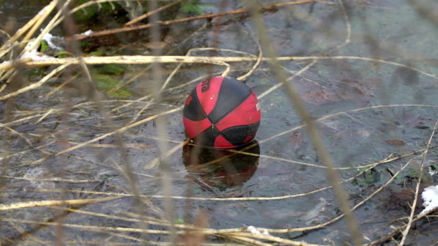 Concept of depressive mood, depression. Forgotten ball in the garden as idea of loneliness. Zoom out video