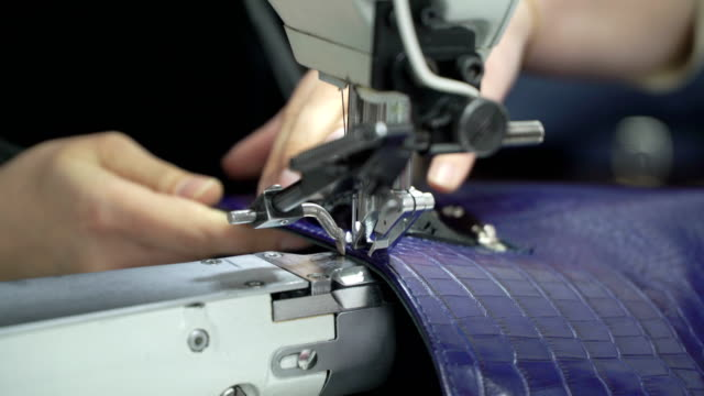 Concept of factory production genuine leather bags. Stitching bag on a sewing machine close up video