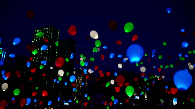 Concept of feast of love. Flying color helium glowing balloons balloons at night city sky video
