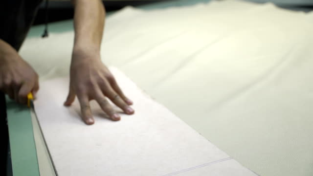 Concept of production genuine leather bags. Cutting leather on the template in the blank area video
