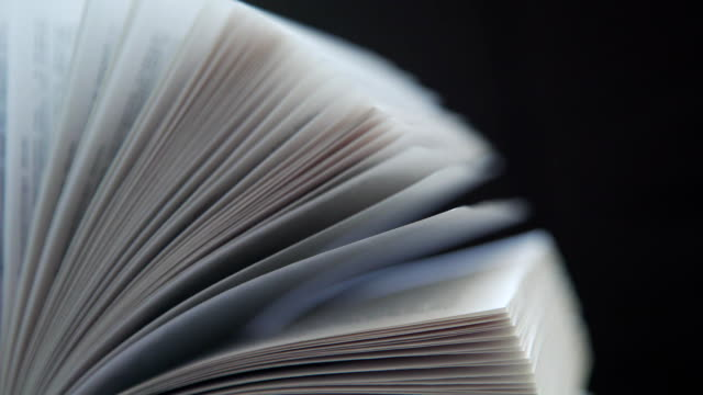 Concept reading, books, flipping books. Book pages on dark background video