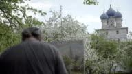 Concept Religion. Skilled Artist Draws Temple in Flowering Garden. Follow Focus video