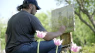 Concept Spring. Skilled Artist Draws Paints of Blossoming Tree. Follow Focus video