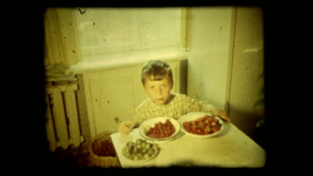 Concept vintage 8 mm film screen with 4 x 3 ratio. Five-year boy eats with pleasure strawberries video