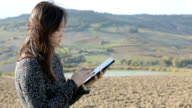 Concept with woman and tablet in Tuscany hill background video