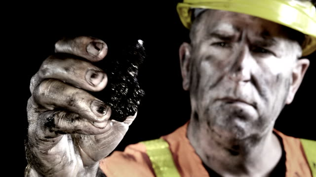 Conceptual video of a coal miner examining a lump of coal just excavated from a mine. video