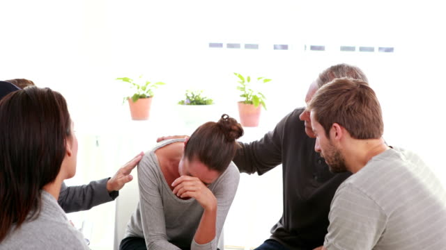 Concerned patients comforting another in rehab group video