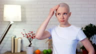 Concerned woman in chemotherapy looking in the mirror and examine herself video
