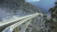 AERIAL: Concrete bridge on mountain pass in winter video