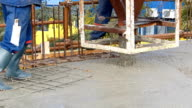 Concrete slab, construction workers work on building video